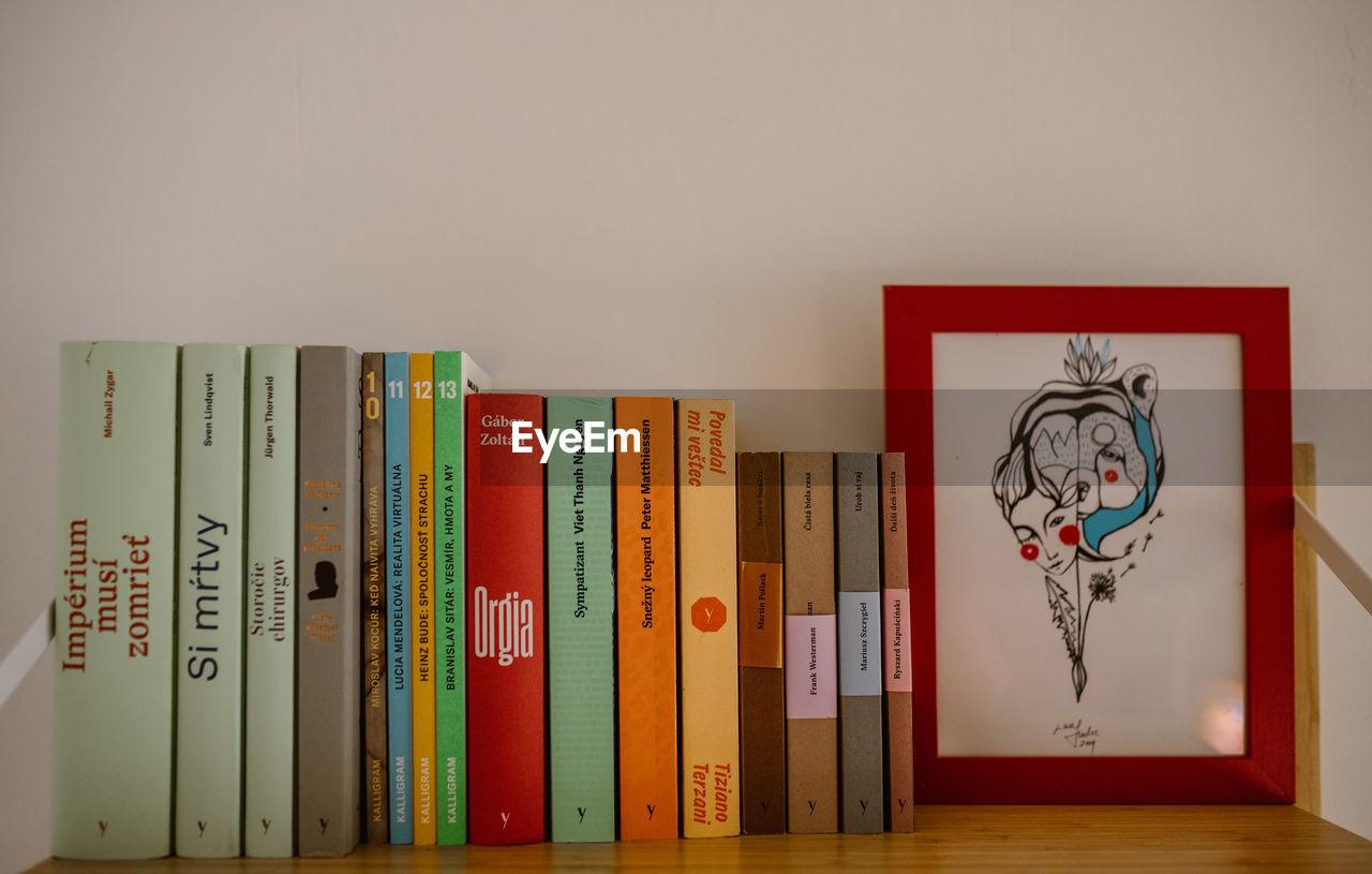 GRAFFITI ON WALL OF BOOKS IN SHELF