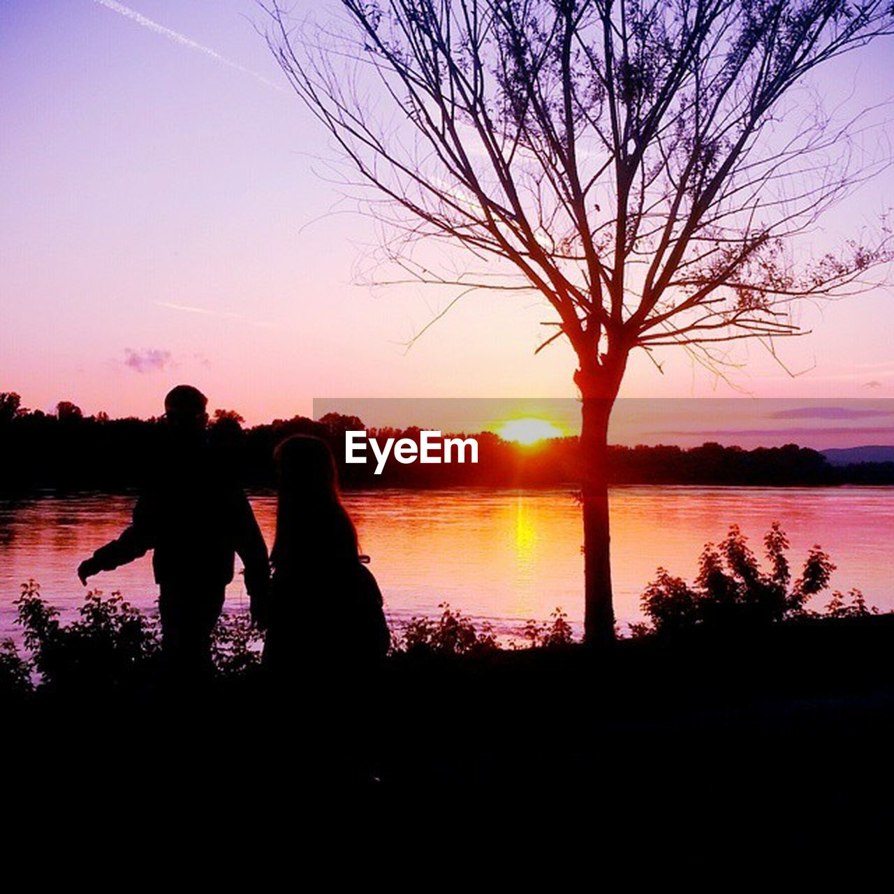 sunset, silhouette, two people, real people, togetherness, nature, leisure activity, women, beauty in nature, lifestyles, water, lake, tree, love, reflection, men, couple - relationship, bonding, sitting, sky, standing, scenics, outdoors, bare tree, adult, people, adults only