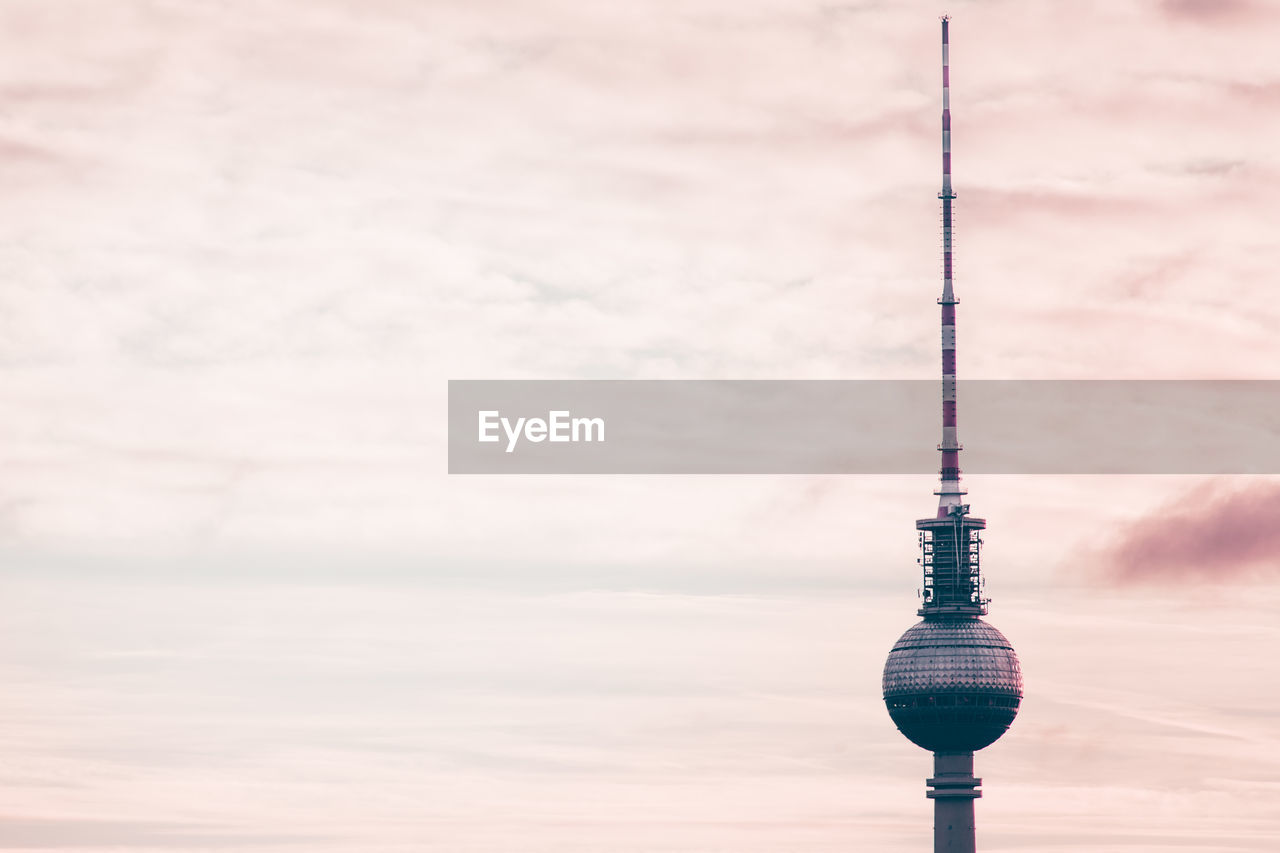 Low angle view of fernsehturm against sky during sunset