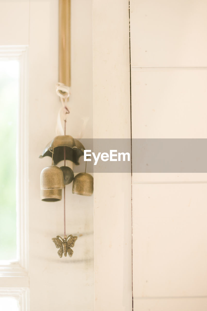 hanging, no people, indoors, wood - material, entrance, door, wall - building feature, architecture, focus on foreground, metal, home interior, built structure, window, day, close-up, lighting equipment, white color, nature, wind chime, ceiling