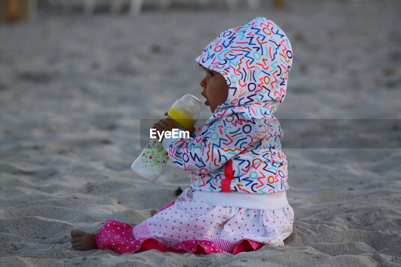 real people, one person, child, childhood, full length, lifestyles, land, women, leisure activity, beach, day, clothing, focus on foreground, females, hat, holding, toy, innocence, water, outdoors, floral pattern