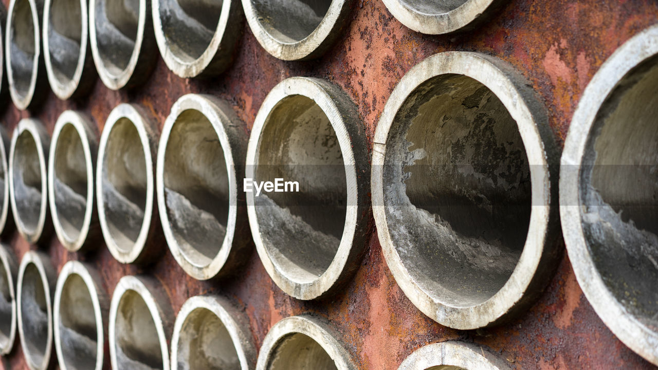 Full Frame Shot Of Cement Pipes In Metallic Wall
