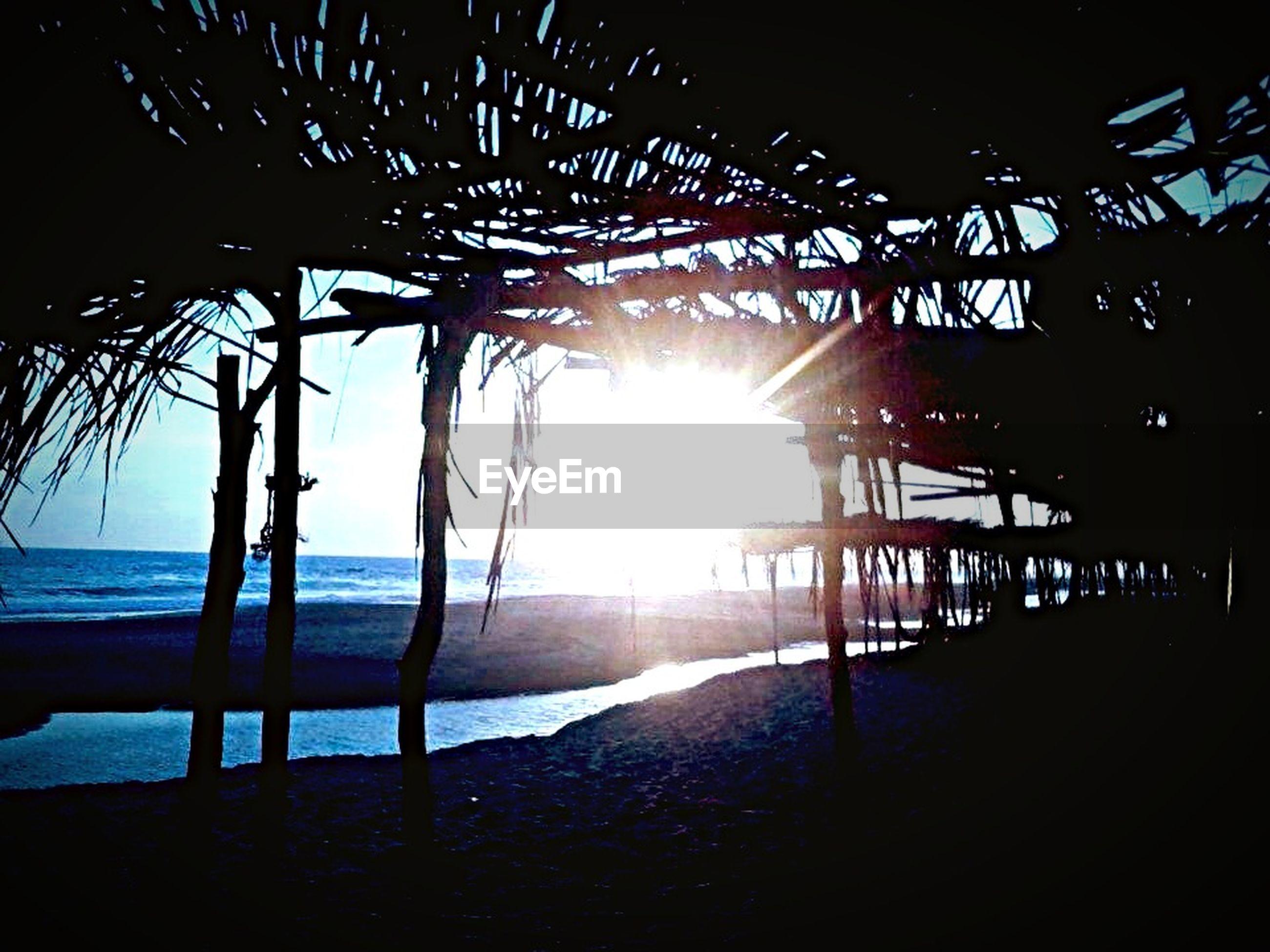 sea, water, sun, beach, horizon over water, shore, sunset, sunbeam, sunlight, scenics, sky, tranquility, beauty in nature, nature, wave, tranquil scene, sand, lens flare, silhouette, pier
