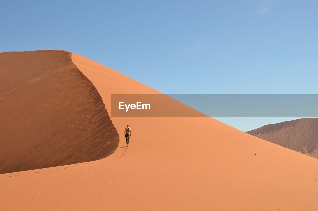 Rear View Of Woman Walking On Sand Dune At Desert