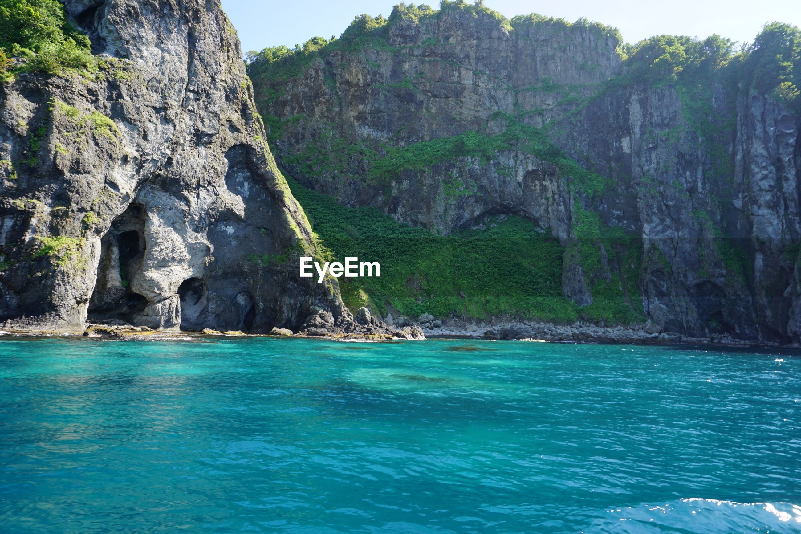 water, rock, solid, sea, nature, rock - object, waterfront, beauty in nature, rock formation, day, scenics - nature, tranquility, cliff, land, tranquil scene, mountain, outdoors, no people, formation, turquoise colored, eroded