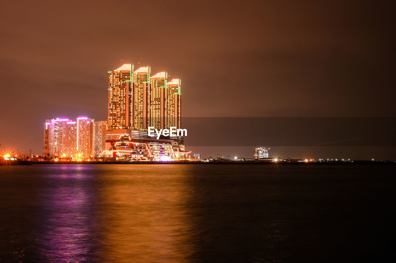 illuminated, night, architecture, built structure, glowing, building exterior, waterfront, travel destinations, sky, celebration, blurred motion, skyscraper, city, no people, outdoors, water, sea, cityscape, urban skyline