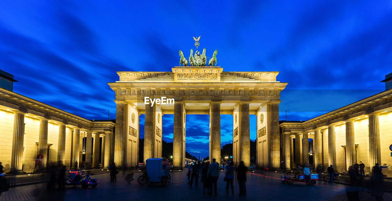 Low angle view of illuminated brandenburg gate against cloudy sky
