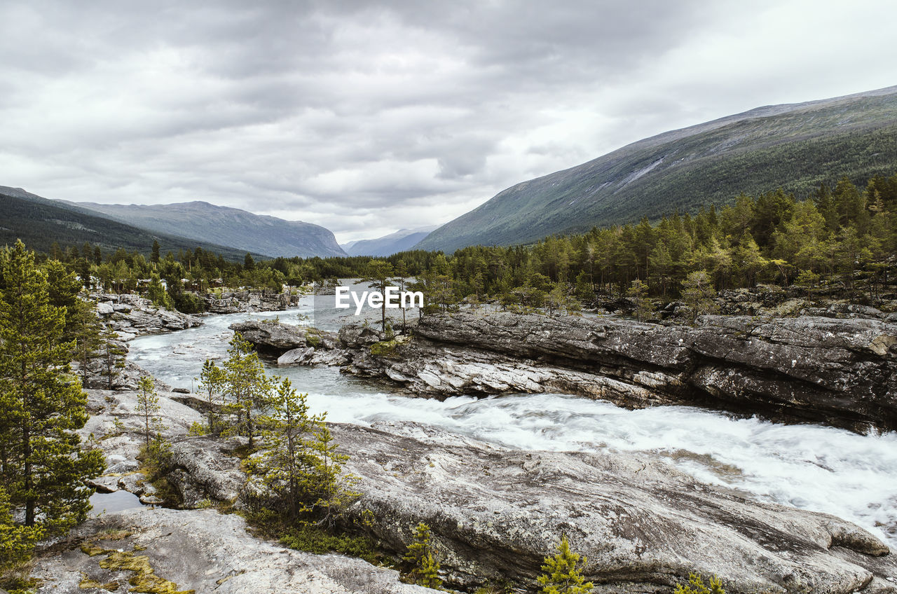 Scenic View Of River And Mountains Against Cloudy Sky