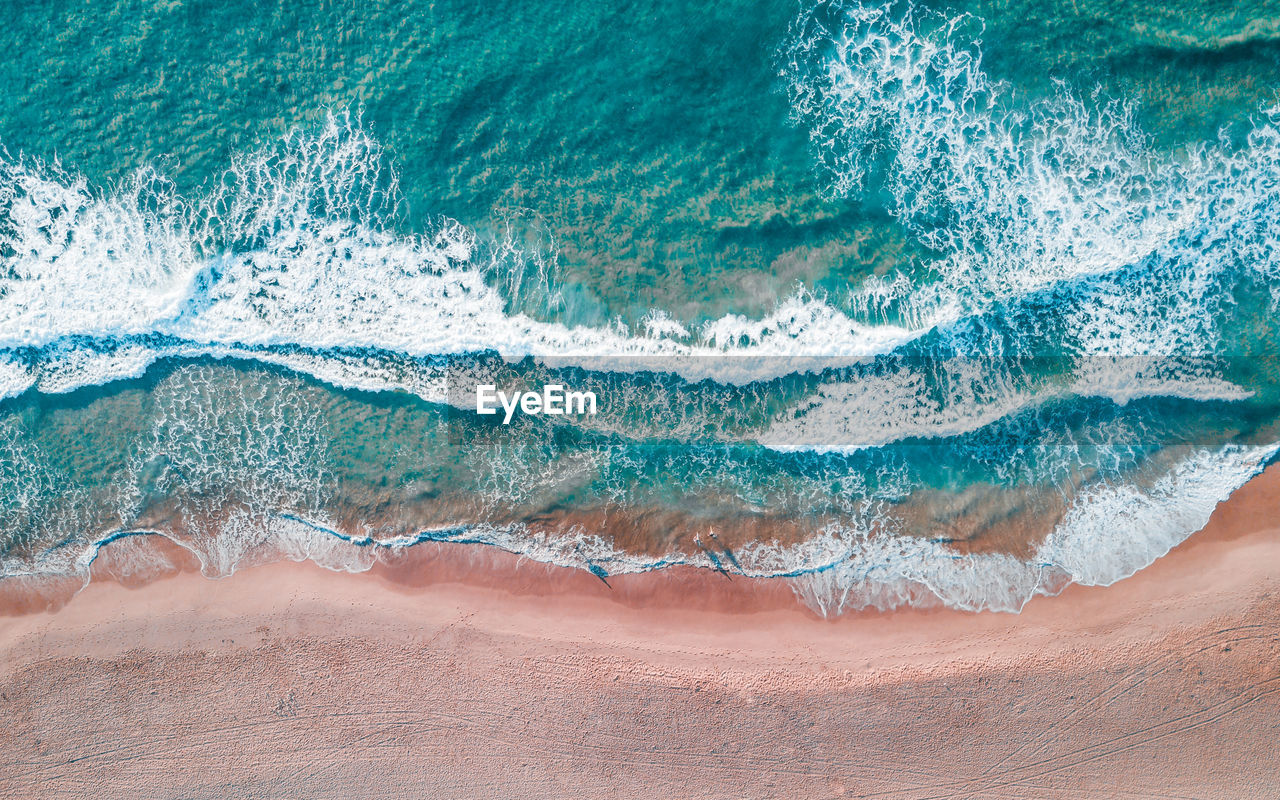 High angle view of waves breaking on the shore of a beach