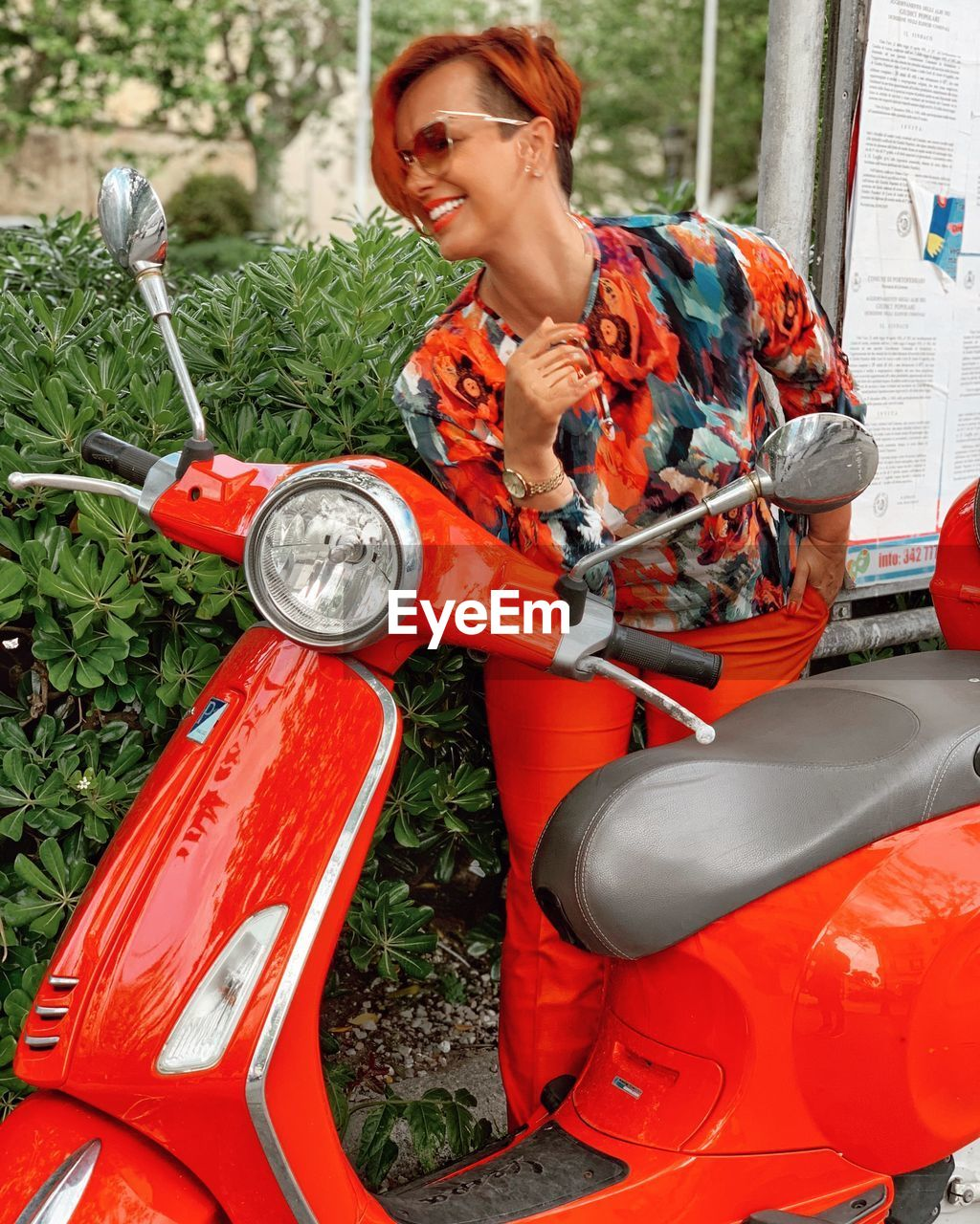 one person, mode of transportation, real people, day, transportation, young adult, front view, three quarter length, lifestyles, holding, females, casual clothing, adult, land vehicle, women, smiling, orange color, outdoors, hairstyle
