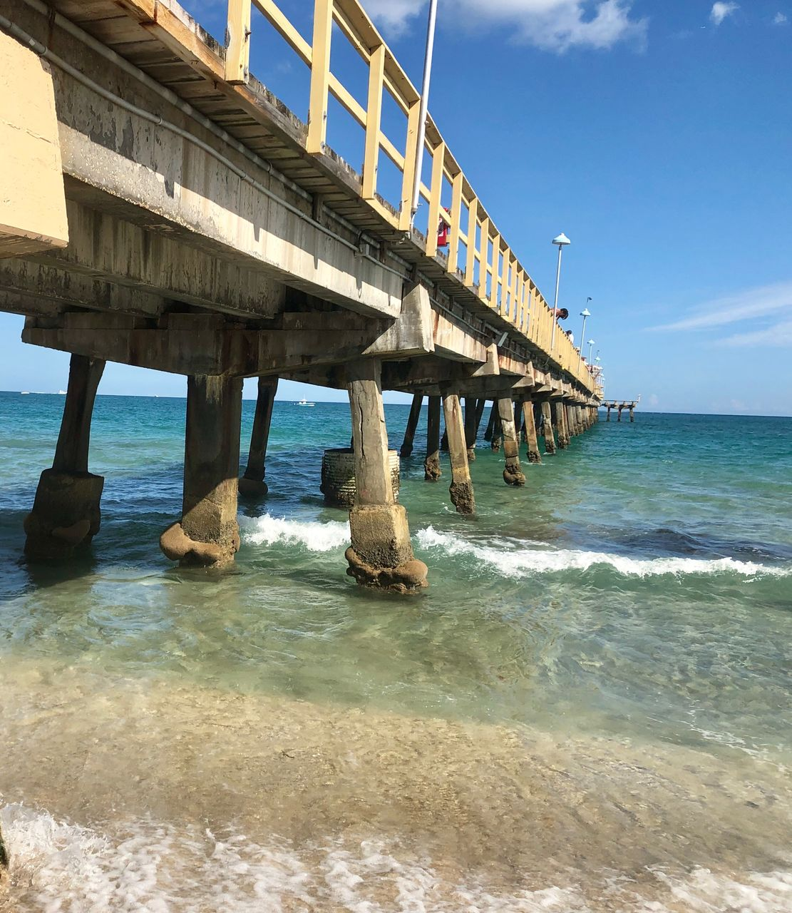 water, sea, built structure, sky, architecture, land, horizon over water, day, beach, nature, scenics - nature, connection, horizon, beauty in nature, bridge, pier, architectural column, wave, motion, no people, bridge - man made structure, outdoors