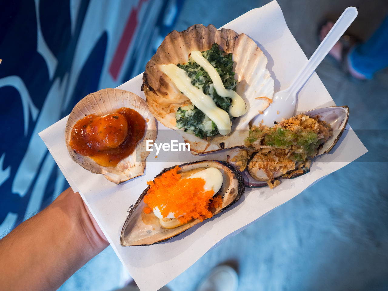 Low Section Of Person Holding Seafood On Paper