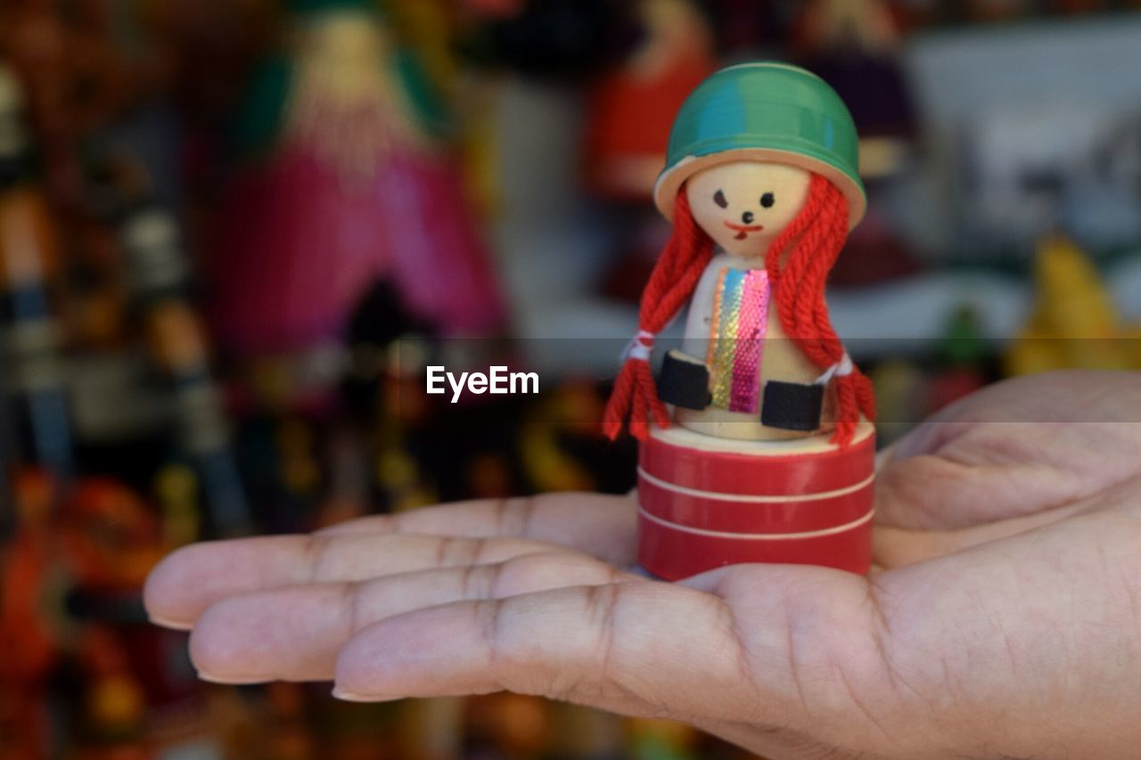 focus on foreground, human hand, holding, close-up, celebration, human body part, one person, figurine, christmas, real people, day, outdoors, christmas decoration, freshness, people