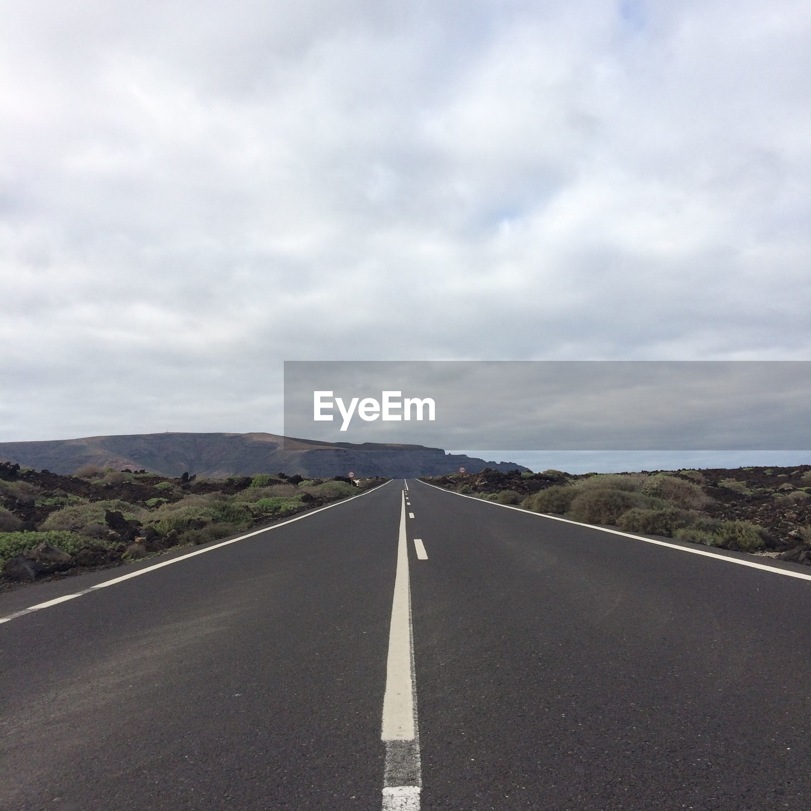 Empty road on field against sky
