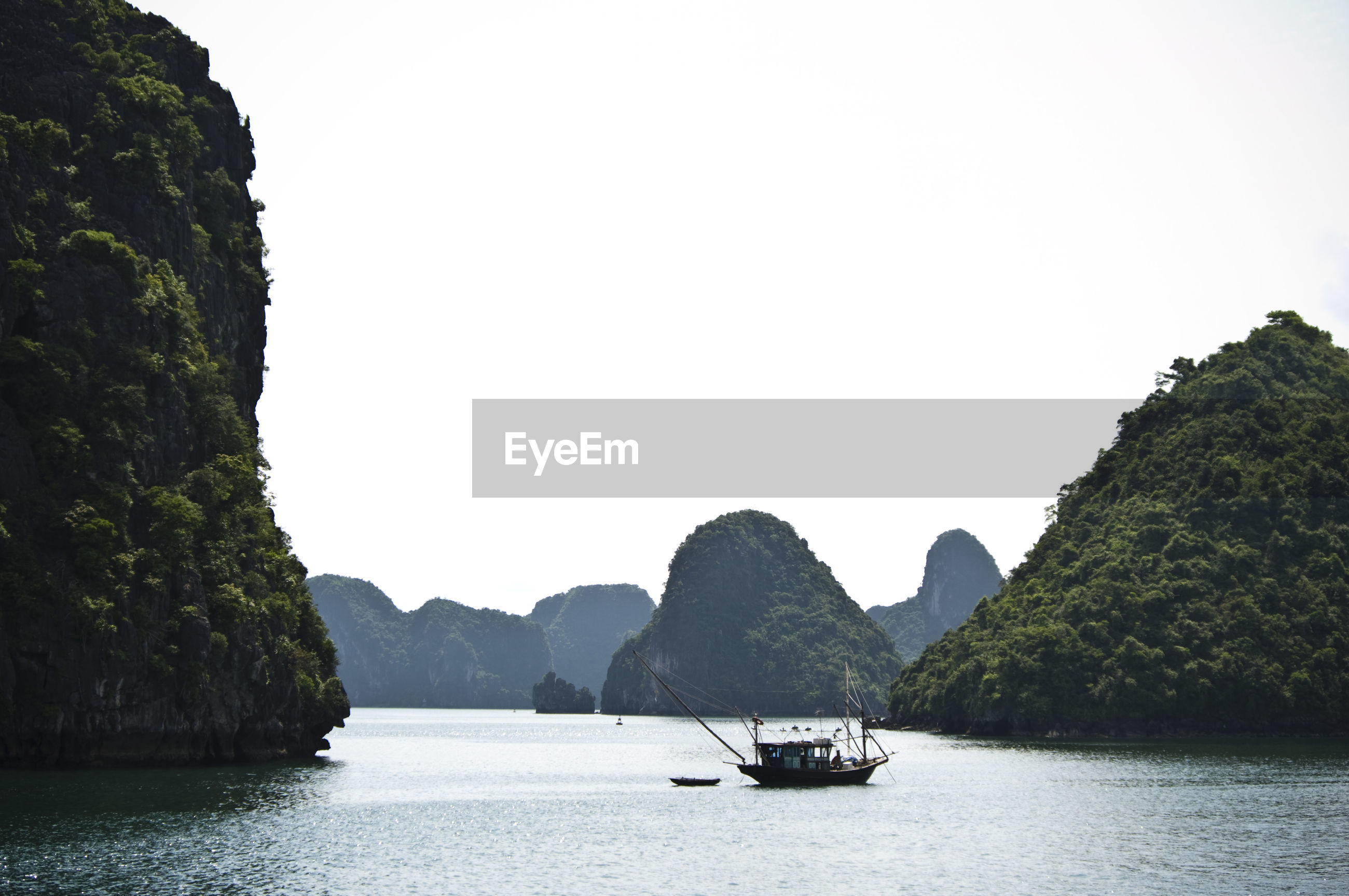 Boat sailing on river against rock formations