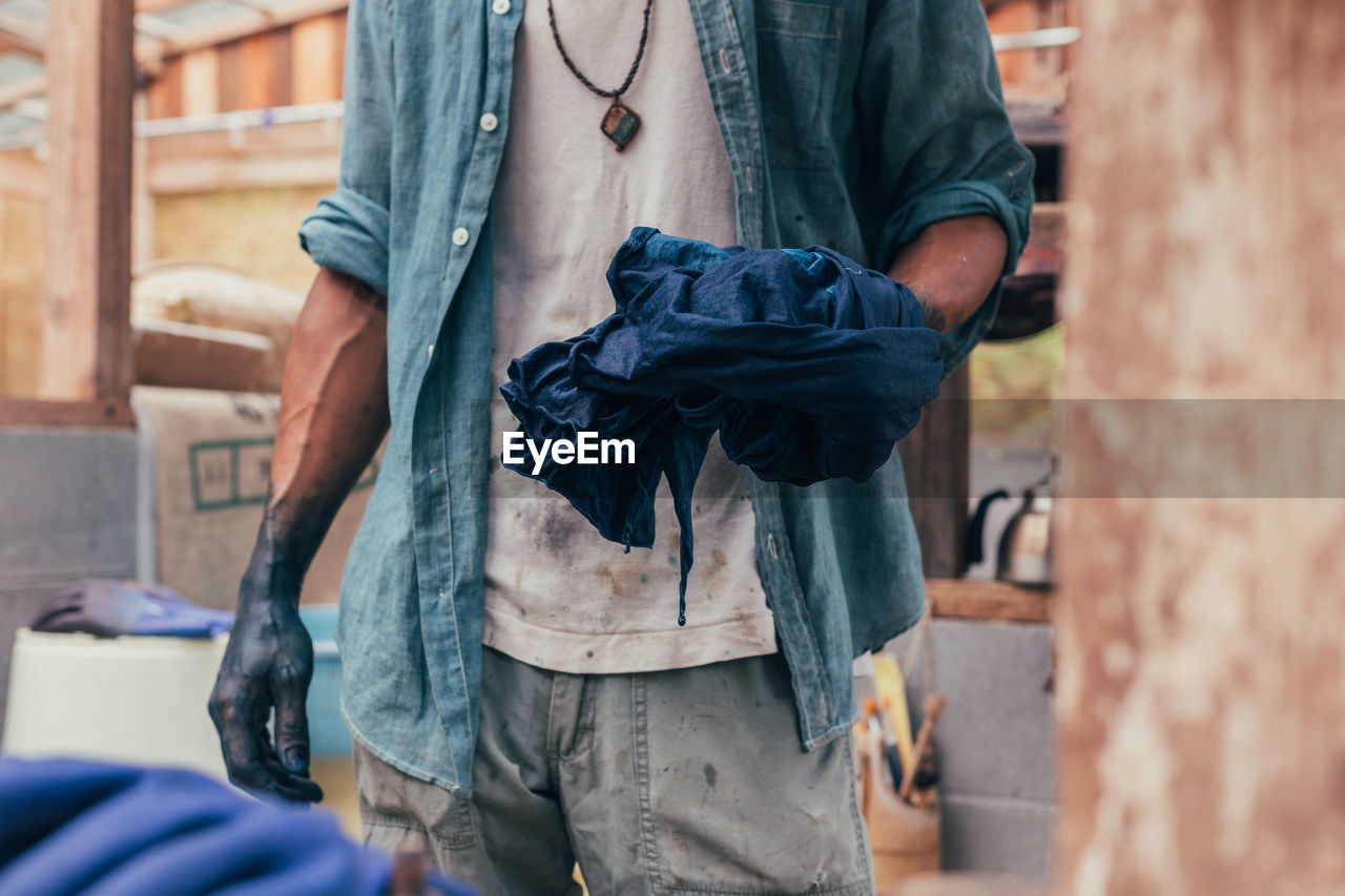 Midsection Of Man Dyeing Clothe In Factory