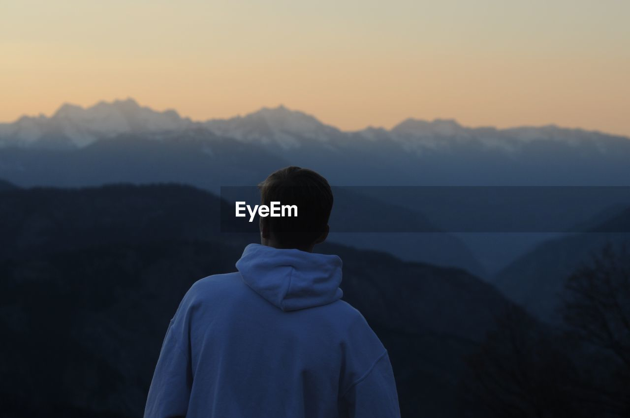 Rear View Of Man Against Mountain During Sunset