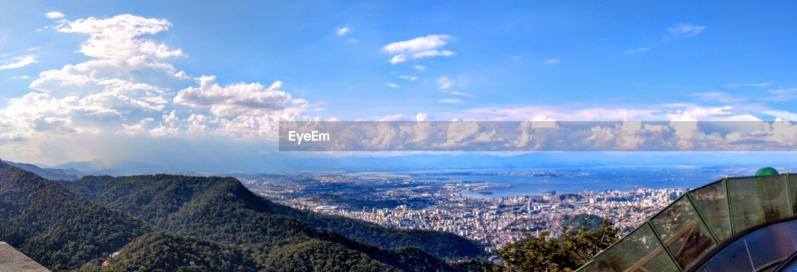 HIGH ANGLE VIEW OF CITYSCAPE AND MOUNTAINS AGAINST SKY