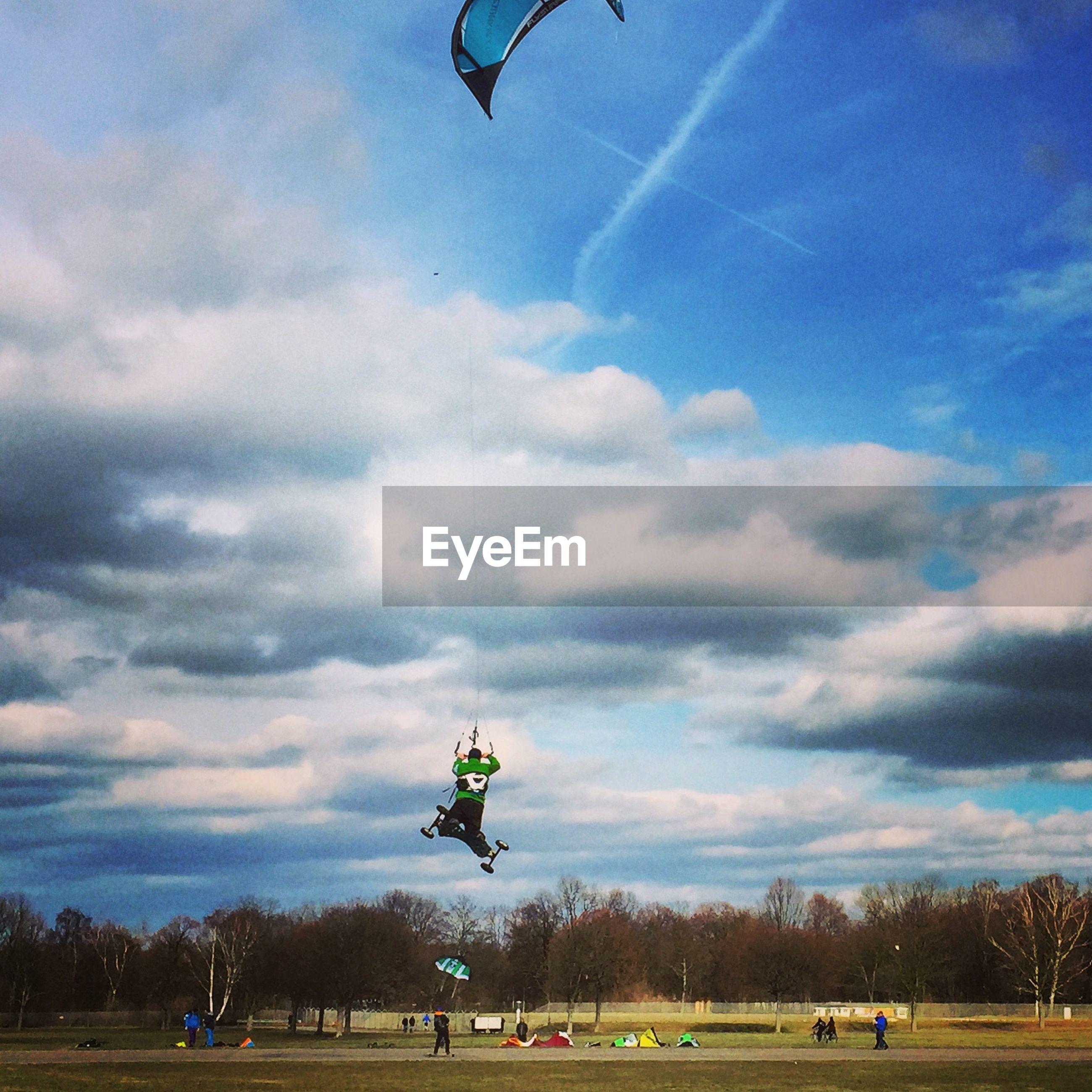 Man with skateboard flying kite