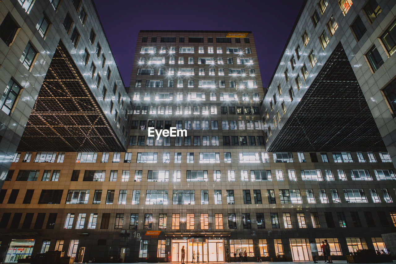 Low angle view of illuminated modern building at night