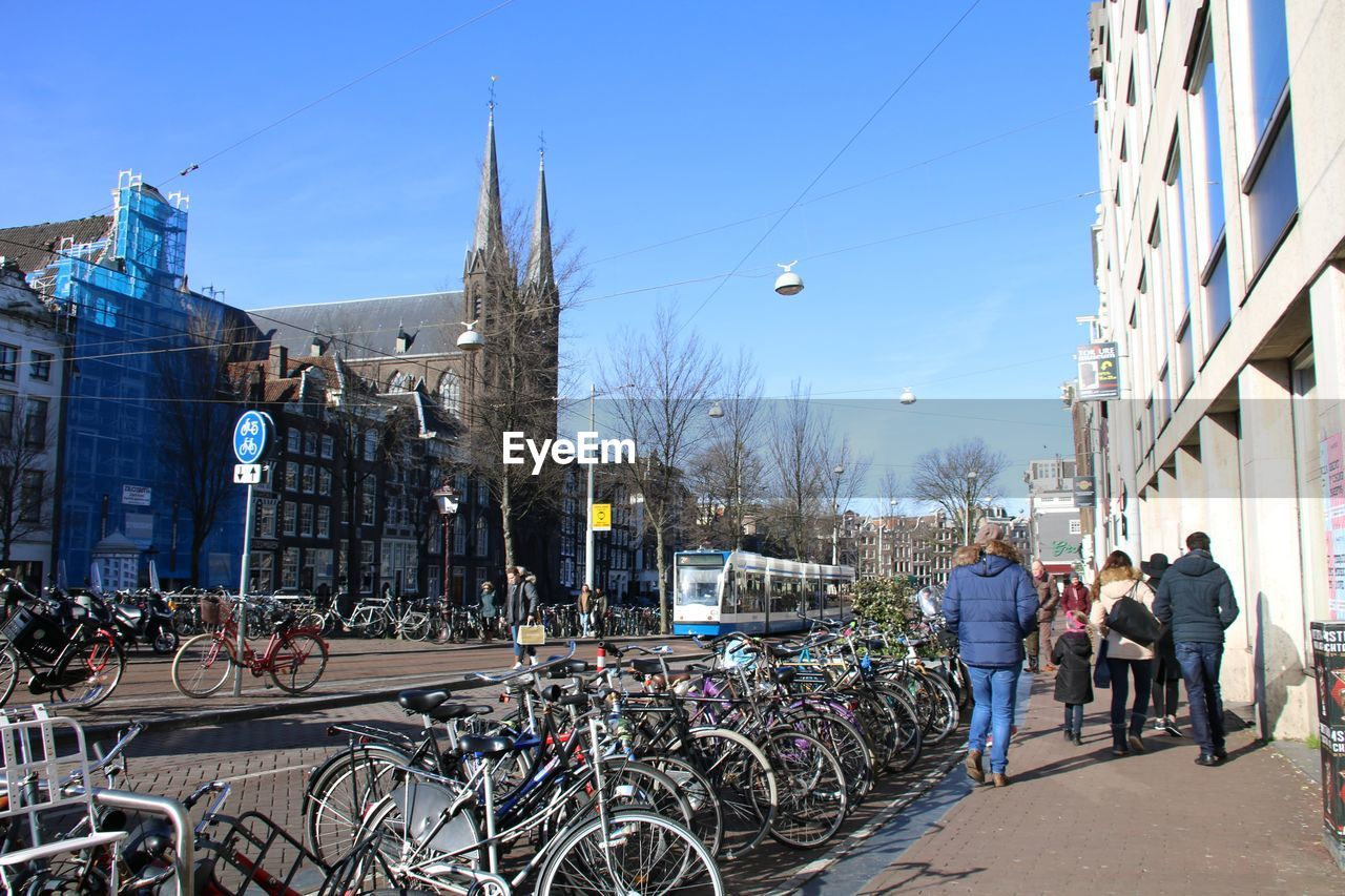 bicycle, architecture, building exterior, built structure, transportation, mode of transport, clear sky, land vehicle, sky, real people, day, large group of people, outdoors, sunlight, men, city, bare tree, cycling helmet, tree, people