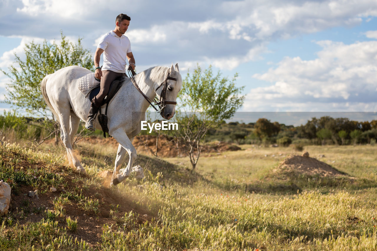 MAN RIDING HORSE IN FIELD