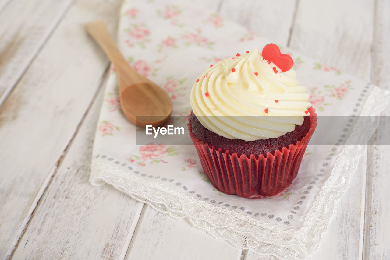 sweet food, indulgence, sweet, cupcake, cake, temptation, dessert, table, ready-to-eat, freshness, food and drink, baked, food, indoors, unhealthy eating, still life, no people, wood - material, focus on foreground, cupcake holder, floral pattern, muffin, snack