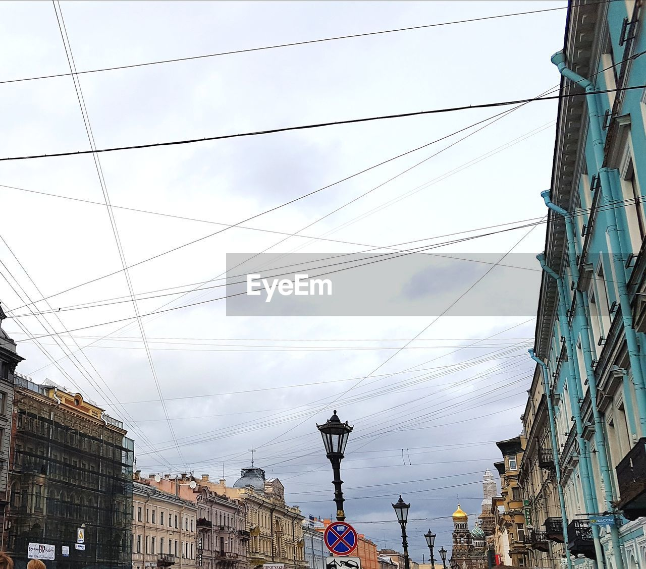 built structure, building exterior, architecture, cable, low angle view, sky, building, city, cloud - sky, day, nature, technology, electricity, connection, power line, residential district, no people, lighting equipment, outdoors, fuel and power generation, power supply