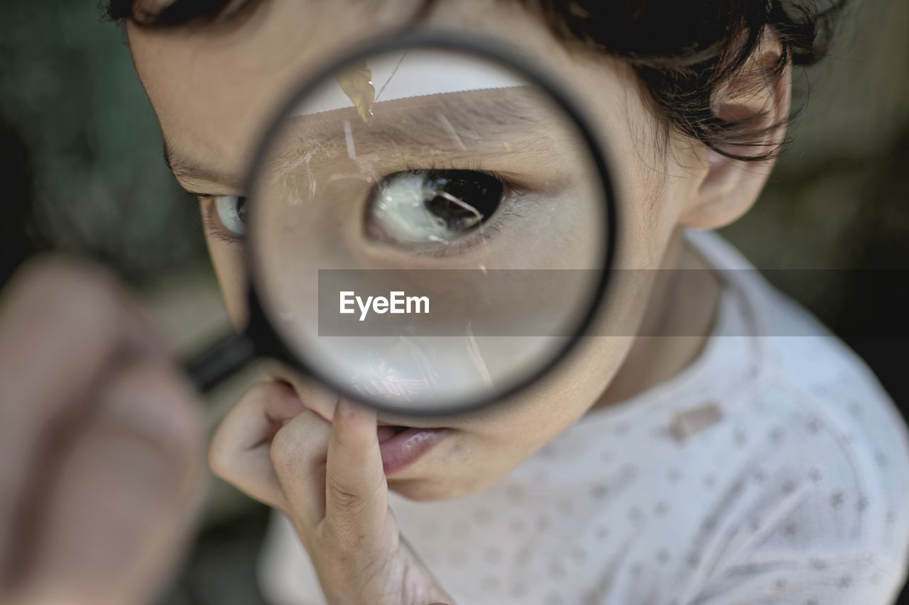 Close-Up Portrait Of Boy Seen Through Magnifying Glass