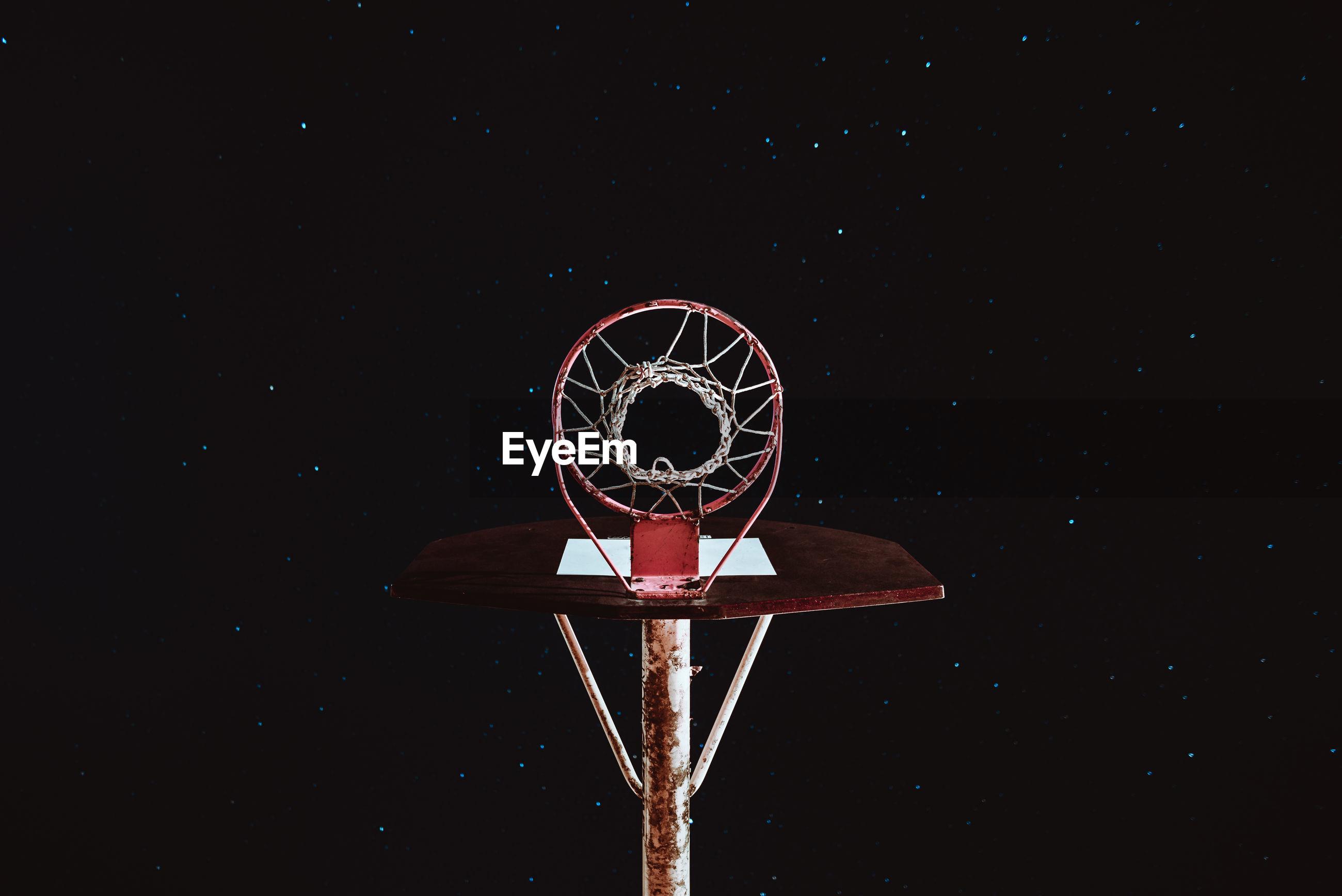 Basketball hoop against sky at night