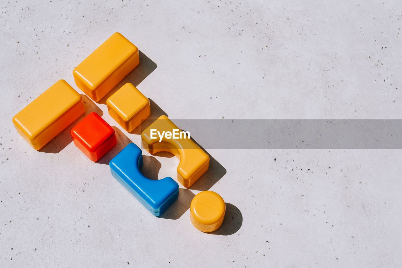 HIGH ANGLE VIEW OF MULTI COLORED TOY ON WHITE BACKGROUND
