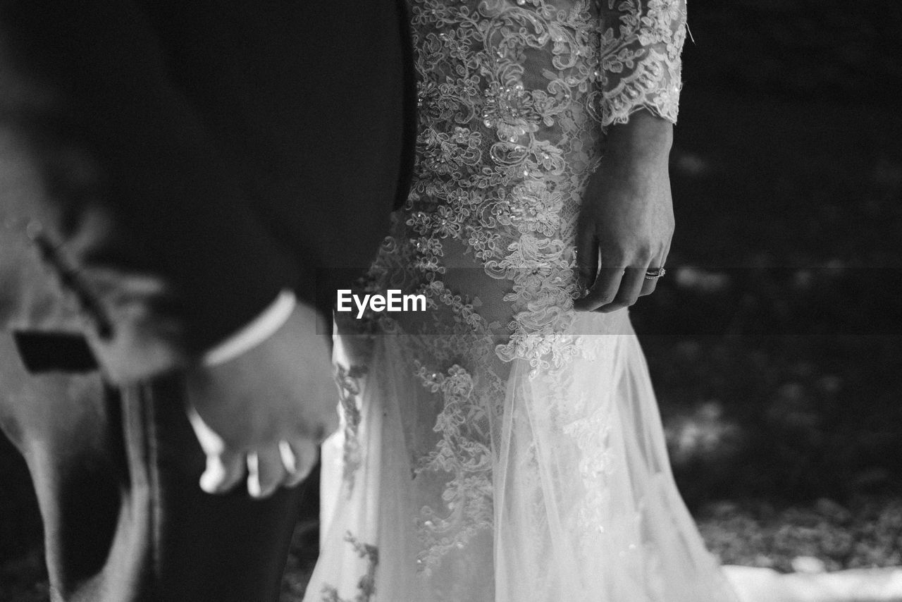 Midsection of newlywed couple standing at wedding ceremony