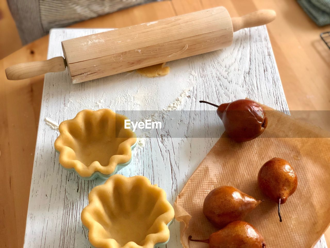 food, freshness, food and drink, table, wood - material, indoors, high angle view, preparation, close-up, still life, cutting board, kitchen utensil, rolling pin, no people, sweet food, preparing food, selective focus, dough, dairy product, healthy eating