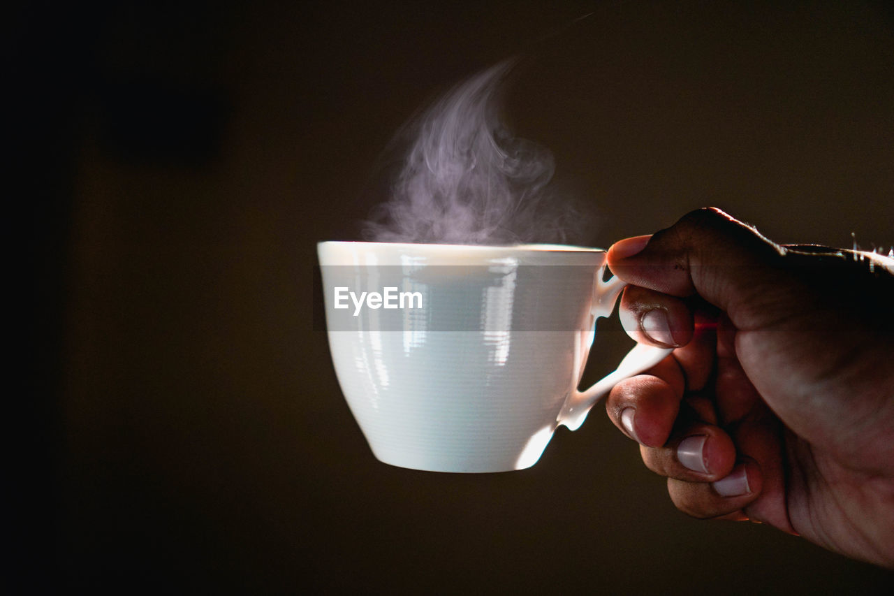 human hand, hand, one person, human body part, cup, holding, real people, mug, coffee cup, smoke - physical structure, indoors, drink, food and drink, lifestyles, unrecognizable person, coffee, body part, refreshment, coffee - drink, finger, tea cup, human limb