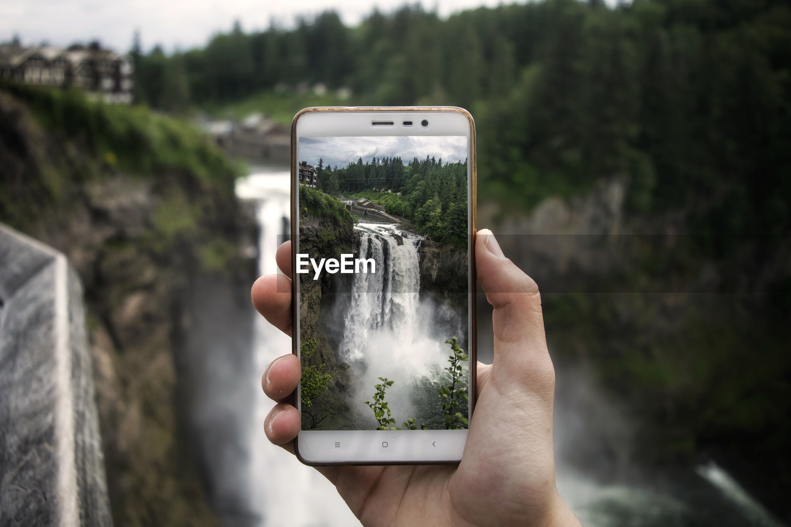 Cropped hand photographing waterfall with mobile phone