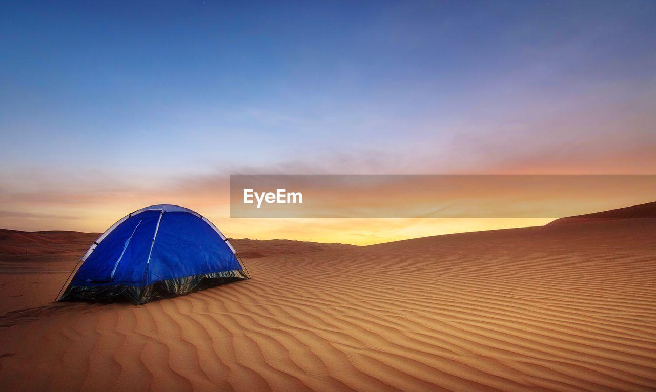 Blue Tent At Desert Against Sky During Sunset