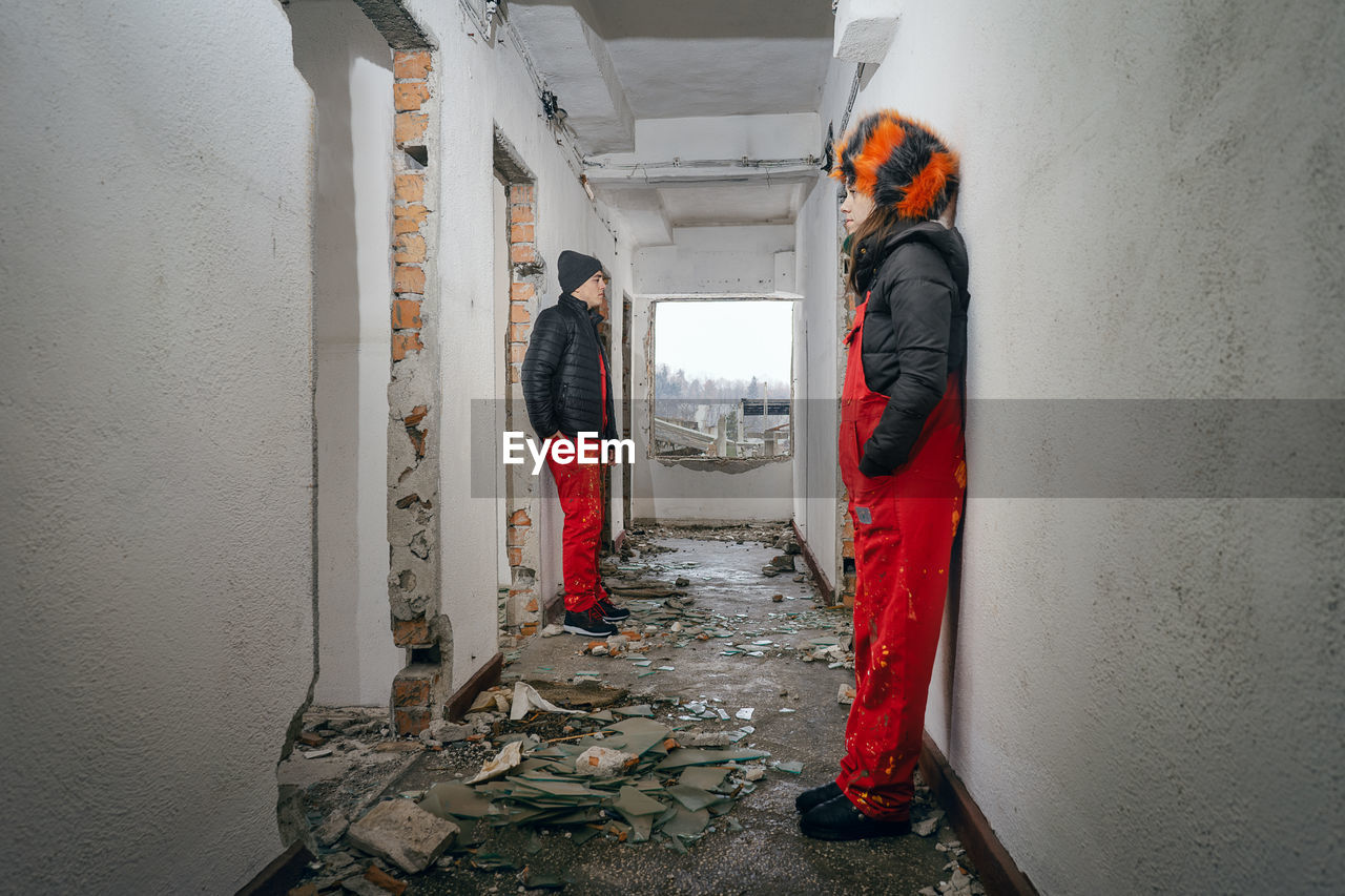 Full Length Of People Standing In Abandoned House