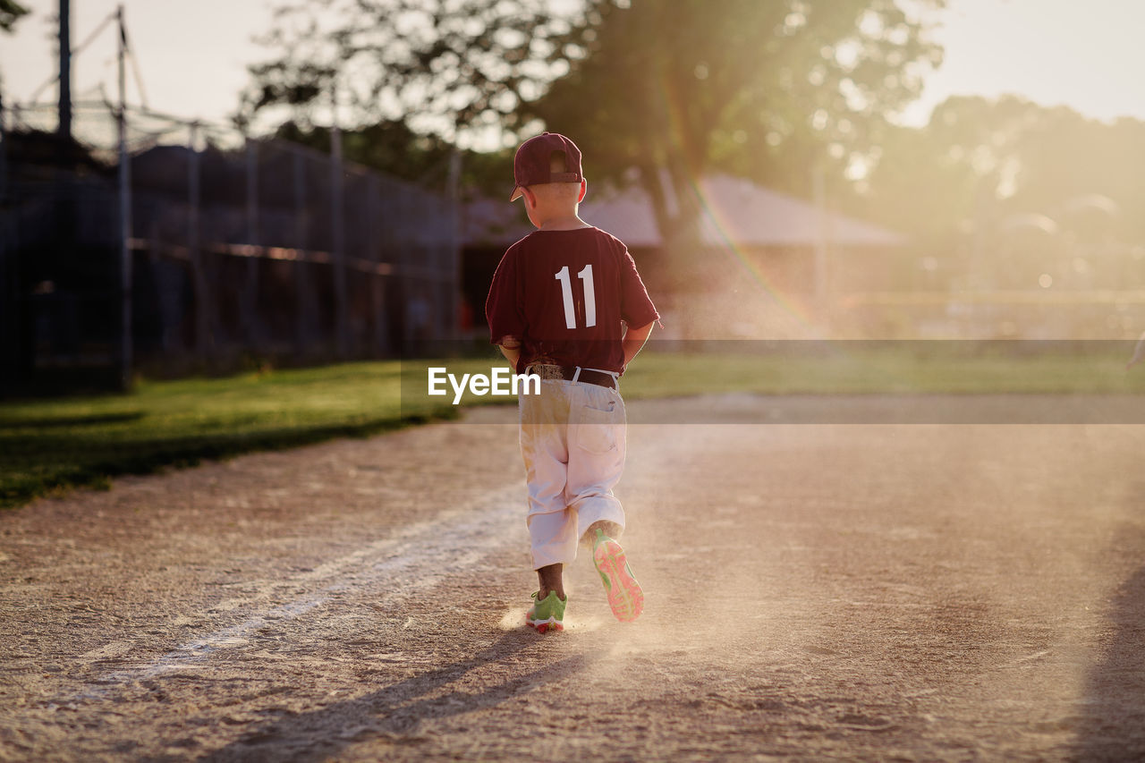 Rear view of boy walking on baseball field