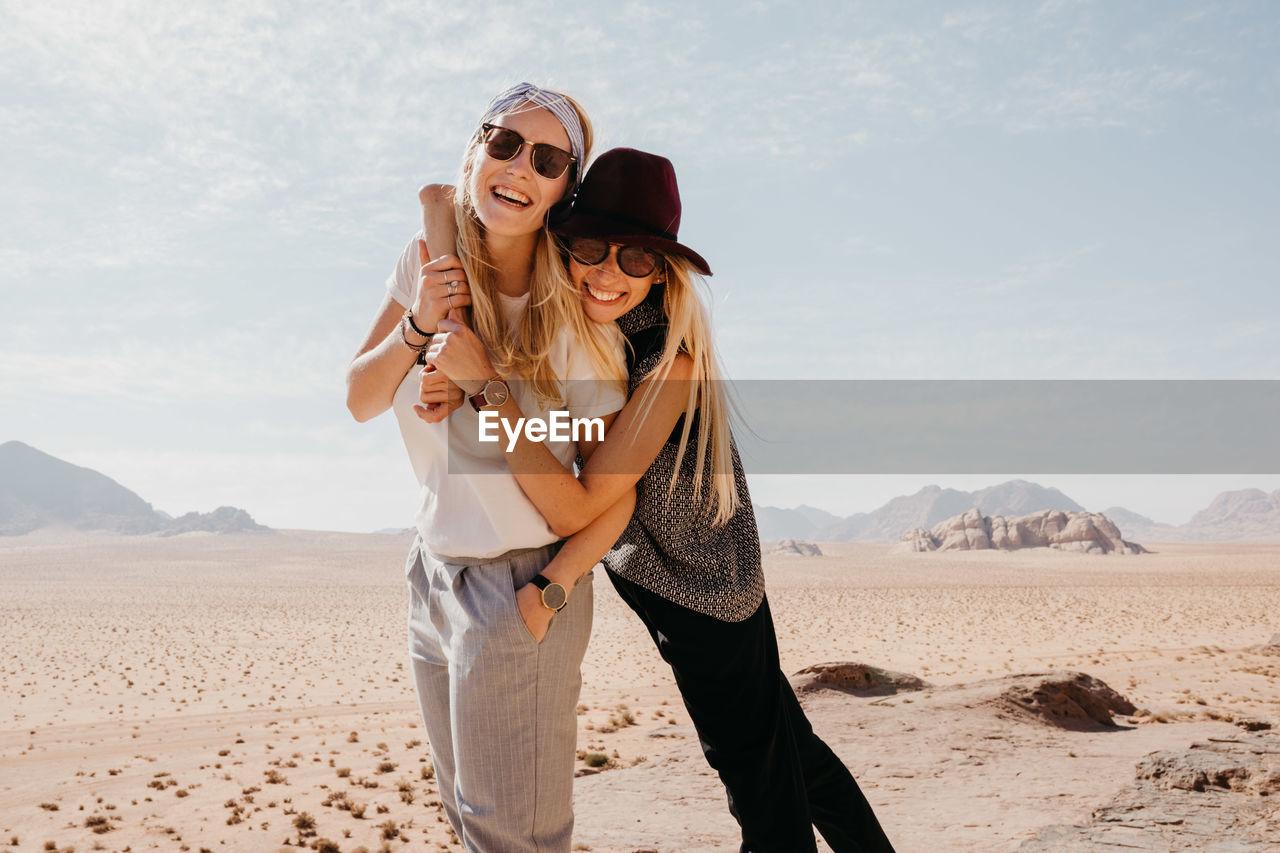 Happy Friends Wearing Sunglasses Standing On Desert Against Sky