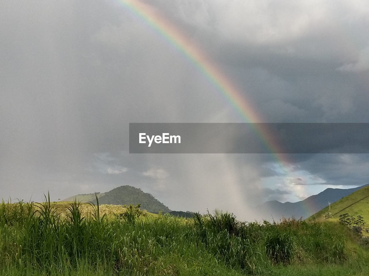SCENIC VIEW OF RAINBOW OVER LAND AND MOUNTAINS AGAINST SKY