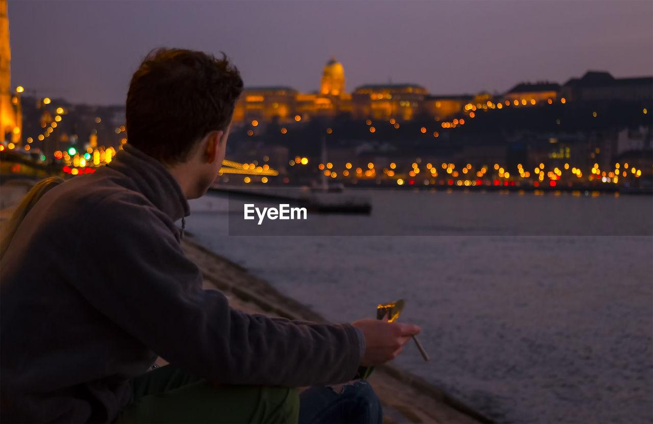 Man sitting on riverbank at night