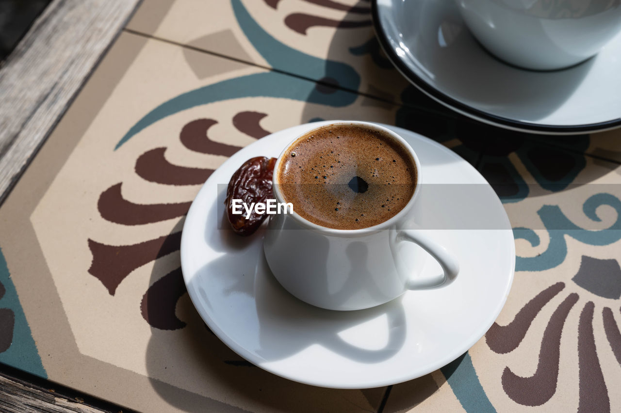 HIGH ANGLE VIEW OF COFFEE CUP ON TABLE WITH TEA