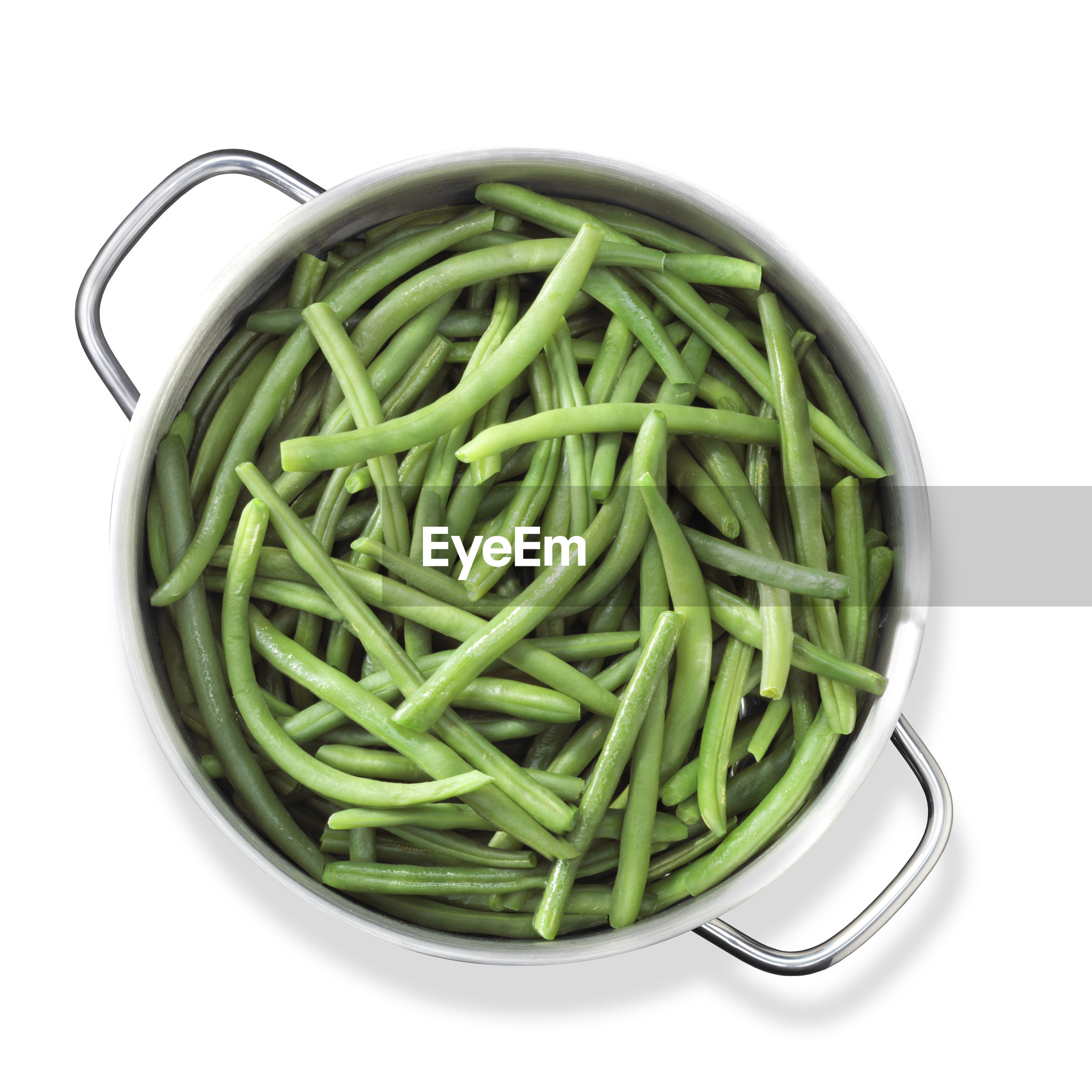 Directly above shot of green beans in container on white background
