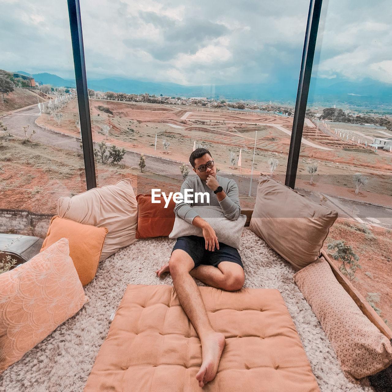 FULL LENGTH OF MAN SITTING ON SOFA AGAINST THE SKY