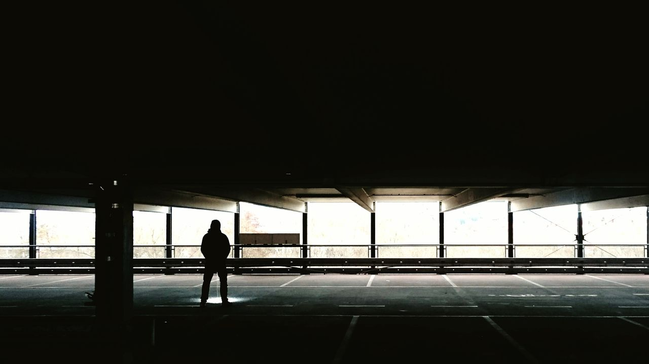 Rear view of silhouette man standing in parking lot