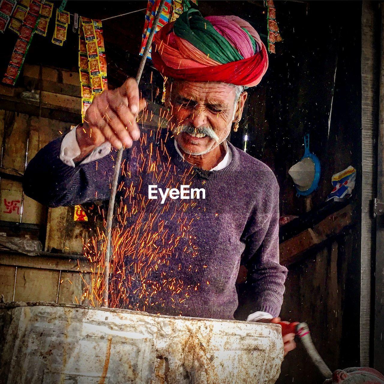 Man Wearing Turban While Preparing Burning Stove At Stall In Market