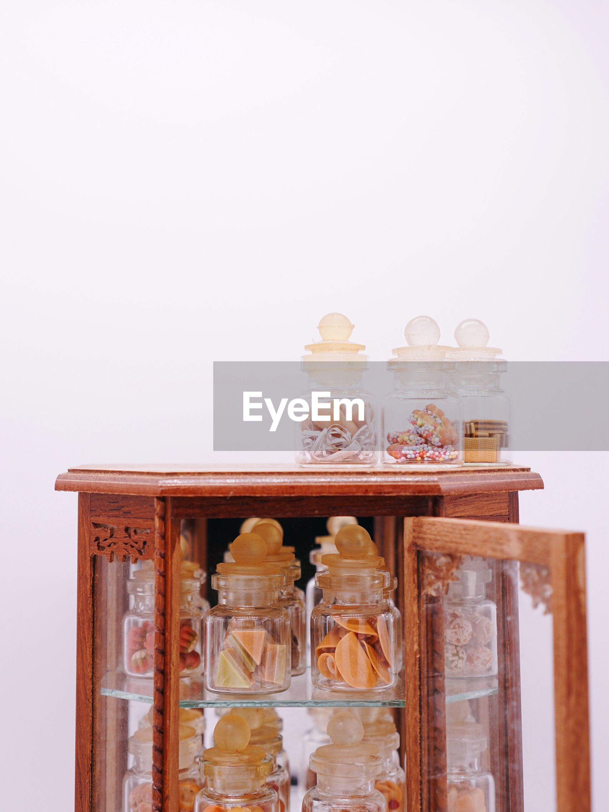 Close-up of glass jars in cabinet against white background