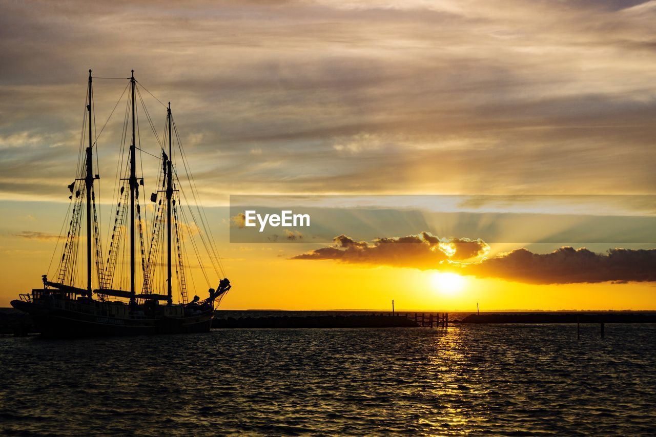 sunset, mast, nautical vessel, water, scenics, nature, beauty in nature, sea, sky, cloud - sky, orange color, sun, transportation, no people, sailboat, mode of transport, tranquility, tranquil scene, silhouette, outdoors, waterfront, sailing, tall ship, sailing ship