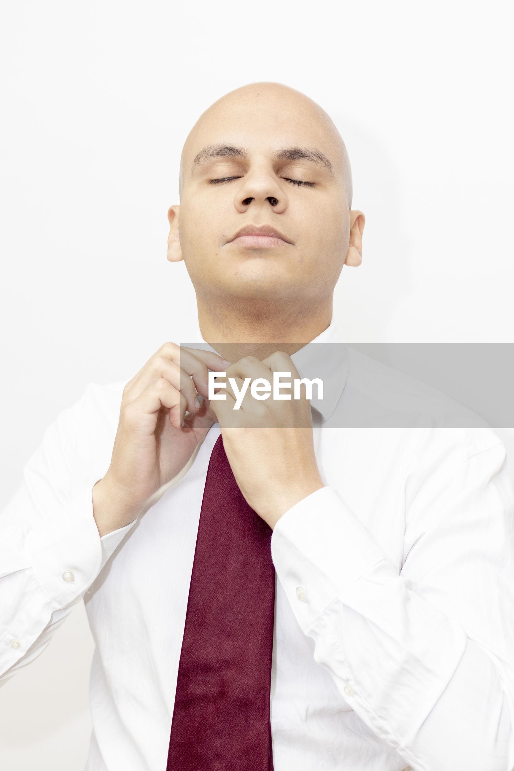 Businessman adjusting necktie against white background