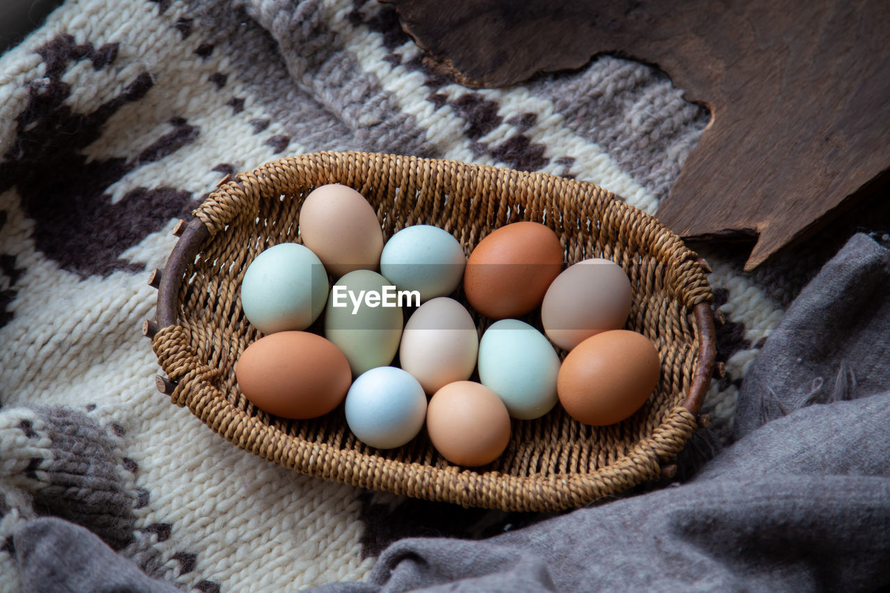 food, no people, food and drink, egg, high angle view, indoors, wellbeing, large group of objects, freshness, healthy eating, close-up, still life, raw food, textile, brown, basket, wood - material, directly above, multi colored, day
